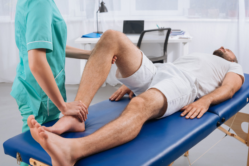 Therapist diagnosing the causes of knee pain