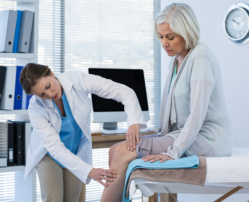 The doctor examines a sore knee